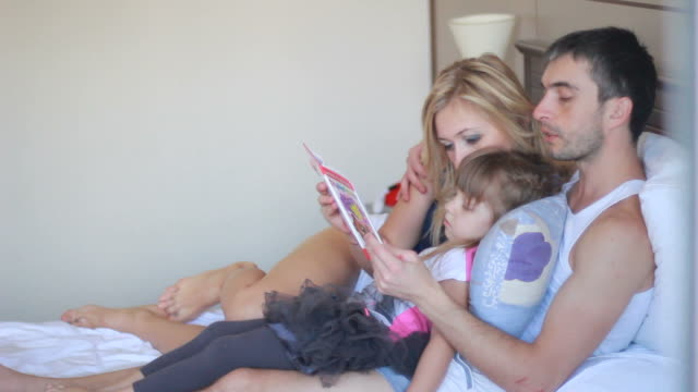 Happy family reading a book in bed video