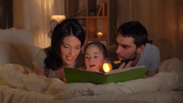 happy family reading book in bed at home people and family concept - happy mother, father and little daughter reading book with torch light in bed at home flashlight stock videos & royalty-free footage