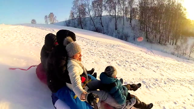 happy family rides and smiling snowtube on snowy roads.slow motion. snow winter landscape. outdoors sports video