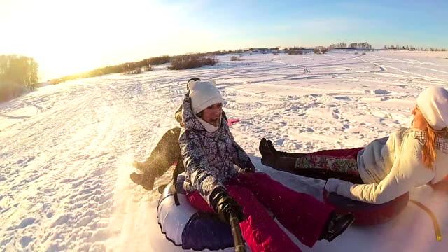 stockvideo's en b-roll-footage met gelukkige familie ritten en lachende snowtube op besneeuwde roads.slow beweging. sneeuw winterlandschap. buiten de sport. zonsondergang - family winter holiday