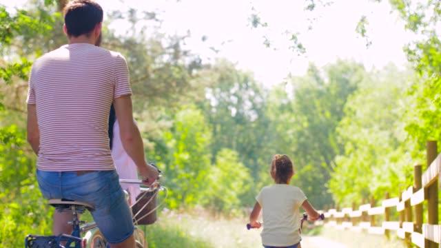 lycklig familj ridning cyklar i sommar park - naturparksområde bildbanksvideor och videomaterial från bakom kulisserna