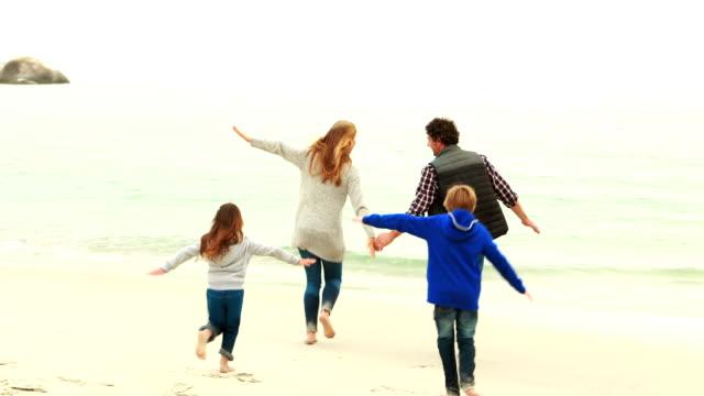 幸せな家族のランニングビーチの ビデオ