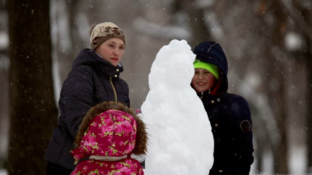 Happy family sculpts snowman out of snow video