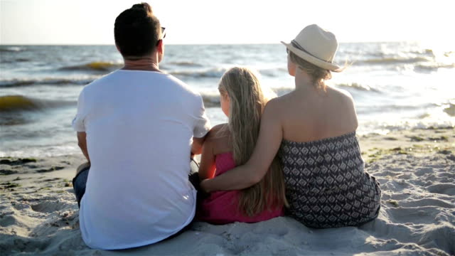 Happy Family Sitting on the Beach, Hugging and Looking on the Waves of the Sea During the Summer Vacation video