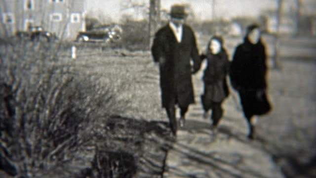1937: Happy family skipping down the sidewalk in wealthy neighborhood. video