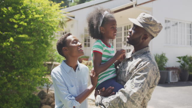 Happy family spending time together Side view of an African American family enjoying time in the garden, a man is wearing military uniform, holding up his daughter, looking at her, on a sunny day, in slow motion military lifestyle stock videos & royalty-free footage