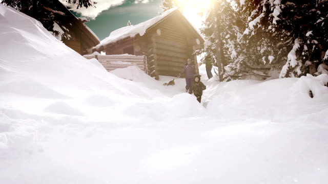 stockvideo's en b-roll-footage met wintervakantie in de berghut met hun hond uitgaven en gelukkige familie - family winter holiday