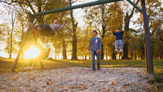 slo mo glückliche familie schwingen in the park - kind schaukel stock-videos und b-roll-filmmaterial