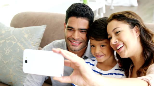 lycklig familj tar en selfie i vardagsrum - enbarnsfamilj bildbanksvideor och videomaterial från bakom kulisserna