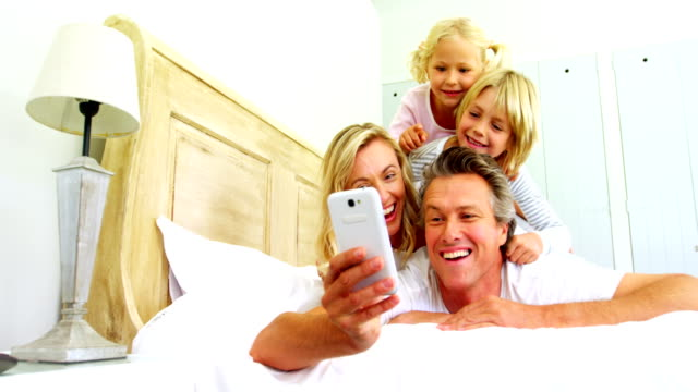 Happy family taking a selfie on mobile phone in the bed room 4k video