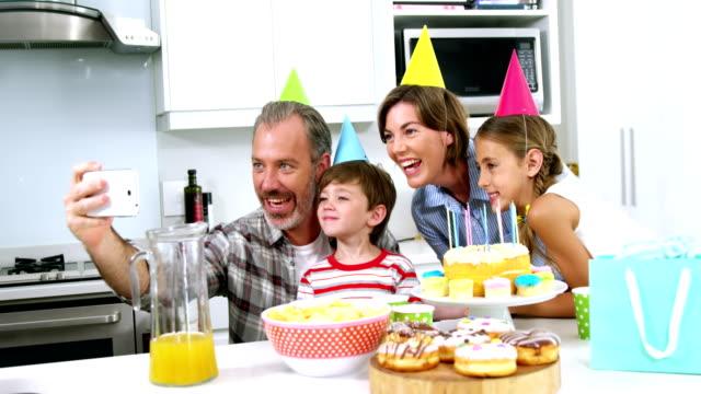 lycklig familj tar en selfie på mobiltelefon - birthday celebration looking at phone children bildbanksvideor och videomaterial från bakom kulisserna