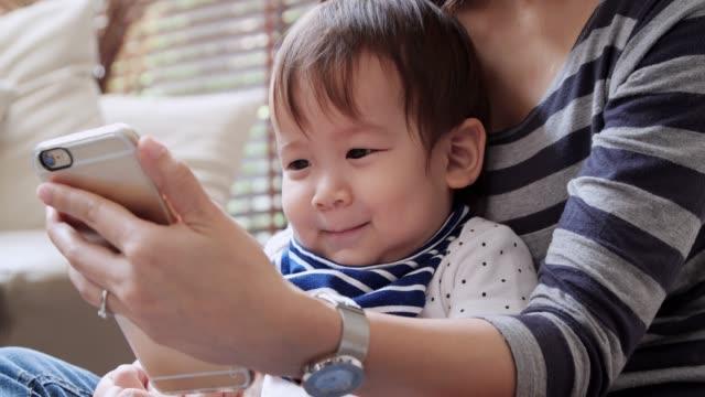 stockvideo's en b-roll-footage met nemen van een selfie met hun baby en gelukkige familie - background baby