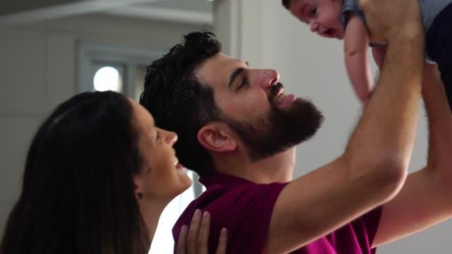happy family insieme al loro nuovo bambino a casa - neonati maschi video stock e b–roll