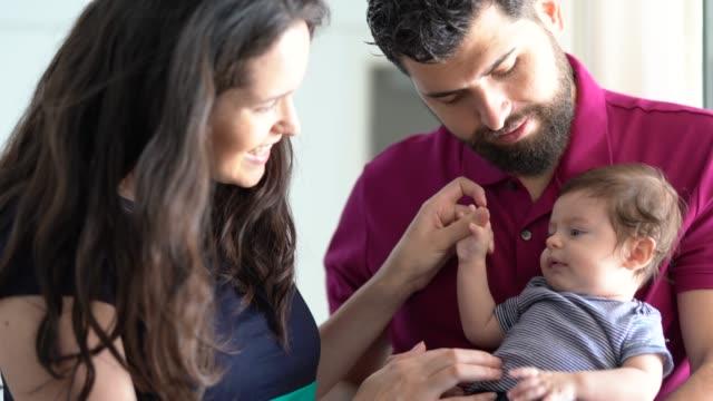 счастливая семья вместе со своим новым ребенком дома - бразилец парду стоковые видео и кадры b-roll