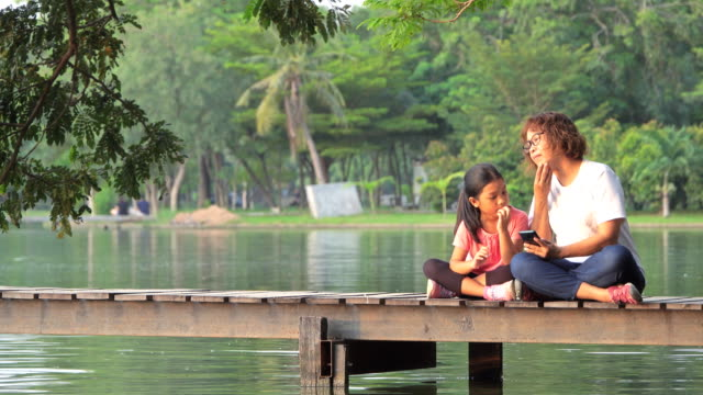 Happy family using Smartphone on a pier by the lake