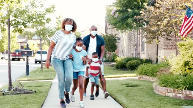 Happy family walk in their neighborhood during the coronavirus pandemic A confident couple with two children walk in their neighborhood to get fresh air and exercise during the COVID-19 pandemic. They are wearing protective face masks while walking in their neighborhood. black people stock videos & royalty-free footage