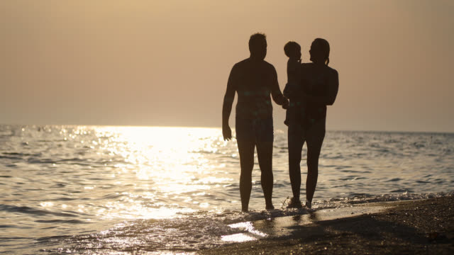 Happy family walking on the beach during beautiful sunset