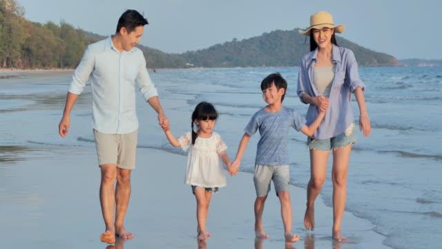 ビーチで一緒に歩く幸せな家族。幸せな家族はビーチで夏休みを楽しみます。バケーション - istock - 息子点の映像素材/bロール