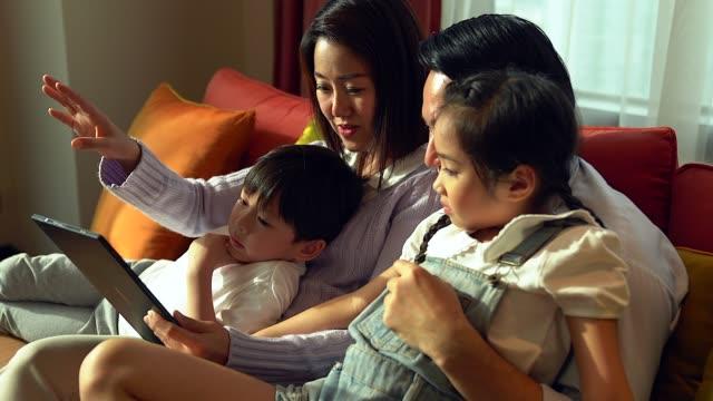 vídeos de stock, filmes e b-roll de família feliz assistindo tablet na sala de estar. - ásia