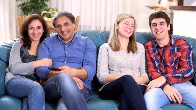 vídeos de stock e filmes b-roll de feliz família a assistir tv e comer pizza em casa - tv e familia e ecrã