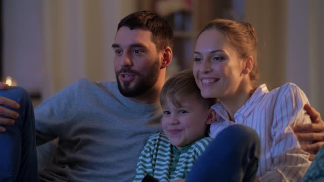 happy family watching tv at home at night family, leisure and people concept - happy smiling father, mother with remote control and little son watching tv at home at night changing channels stock videos & royalty-free footage