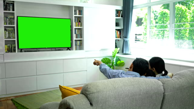 4K Happy Family Watching TV With Green screen Monitor In Living Room 4K Smiling Father, Mother And Son Using Remote Control Turns It Channel To Green Screen Monitor For Your Message family watching tv stock videos & royalty-free footage