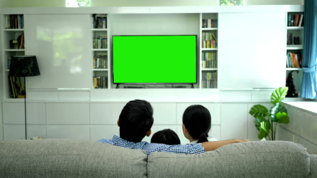 Happy Family Watching TV With Green screen Monitor In Living Room 4K Smiling Father, Mother And Son Using Remote Control Turns It Channel To Green Screen Monitor For Your Message family watching tv stock videos & royalty-free footage