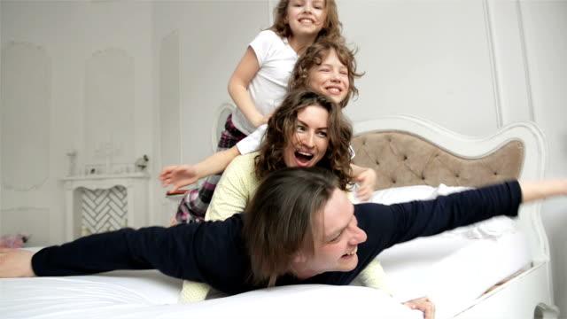 lycklig familj iklädd pyjamas är att ha kul i sovrummet. två playfull barn med lockigt hår och unga par är njuter av helgen ligga tillsammans på vit säng - cosy pillows mother child bildbanksvideor och videomaterial från bakom kulisserna
