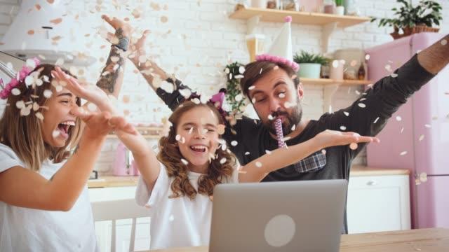 lycklig familj med en dotter firar födelsedag i köket med hjälp av laptop för ett videosamtal under online födelsedagsfest. familj kastar konfetti och ha kul, slow motion - birthday celebration looking at phone children bildbanksvideor och videomaterial från bakom kulisserna