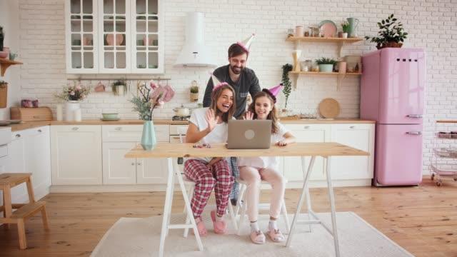 lycklig familj med en dotter firar födelsedag i köket med hjälp av laptop för ett videosamtal under online födelsedagsfest, slow motion - birthday celebration looking at phone children bildbanksvideor och videomaterial från bakom kulisserna