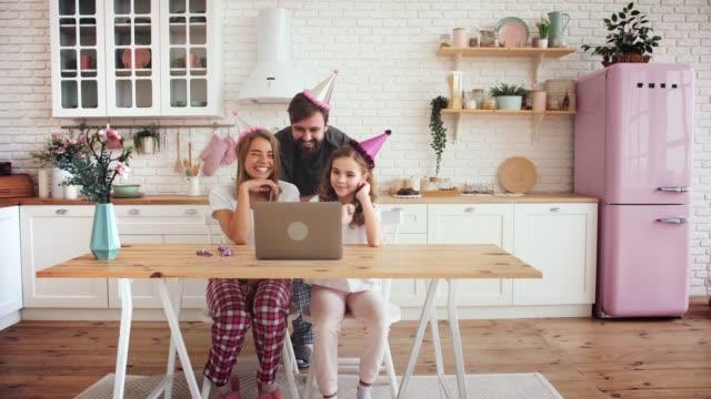 lycklig familj med en dotter firar födelsedag i köket med hjälp av laptop för ett videosamtal under online födelsedagsfest. karantäntid, självisolering, socialt avståndstagande - birthday celebration looking at phone children bildbanksvideor och videomaterial från bakom kulisserna