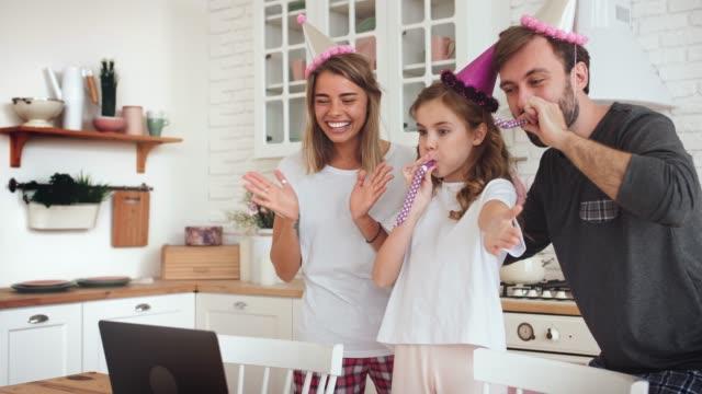lycklig familj med en dotter firar födelsedag i köket med hjälp av laptop för ett videosamtal under online födelsedagsfest och ha lite kul, slow motion - birthday celebration looking at phone children bildbanksvideor och videomaterial från bakom kulisserna