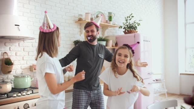 lycklig familj med en dotter i pyjamas firar födelsedag i köket under online födelsedagsfest och ha lite kul, slow motion - birthday celebration looking at phone children bildbanksvideor och videomaterial från bakom kulisserna