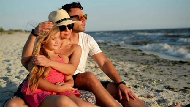 Happy Family with a Daughter on Vacation Sitting at the Beach. Smiling Parents in Sunglasses with a Kid Enjoying Sunset video