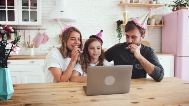 lycklig familj med en dotter som sitter i köket och firar födelsedag med hjälp av laptop för ett videosamtal under online födelsedagsfest och ha lite kul, slow motion - birthday celebration looking at phone children bildbanksvideor och videomaterial från bakom kulisserna
