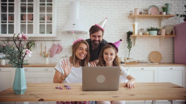 lycklig familj med en dotter viftande händer och fira födelsedag i köket med hjälp av laptop för ett videosamtal under online födelsedagsfest - birthday celebration looking at phone children bildbanksvideor och videomaterial från bakom kulisserna