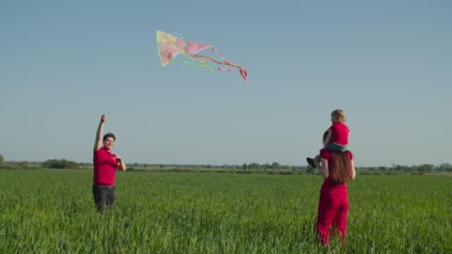 Happy family with baby playing with kite outdoors