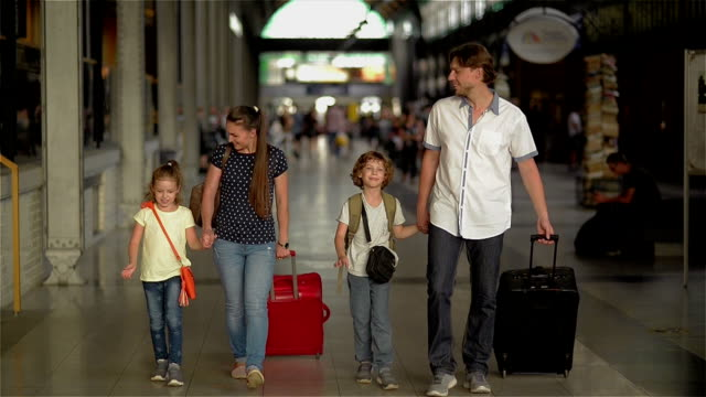 Happy family with children going on railway station, parents and kids traveling and walking on the airport video