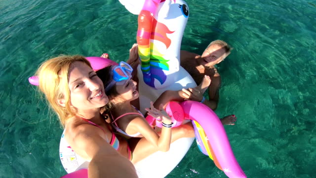 Happy family with girl taking selfie in the sea seating on the inflatable unicorn