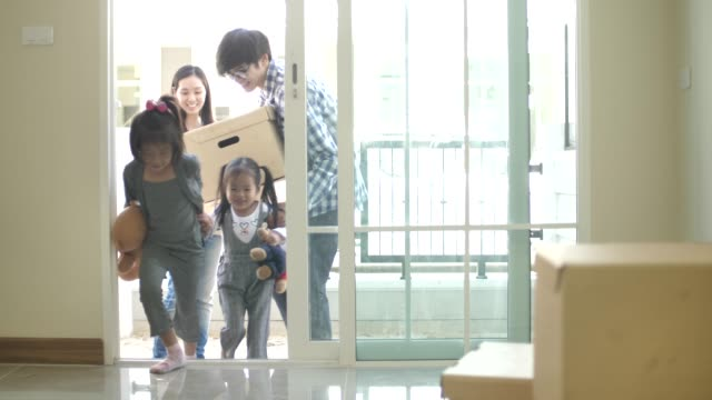 happy family with kids holding boxes entering new modern house - attività fisica video stock e b–roll