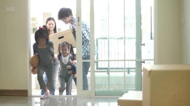 lycklig familj med barn som håller rutorna ange nya moderna hus - omlokalisering bildbanksvideor och videomaterial från bakom kulisserna