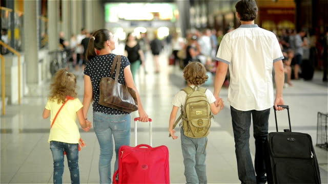 Happy family with little girl and boy going on railway station, mother father and the kids walk through the airport with suitcases video