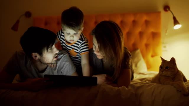 vídeos de stock, filmes e b-roll de família feliz com filho pequeno e engraçado gato deitado na cama em casa e usando computador tablet para assistir filme de desenho animado antes de dormir - felino