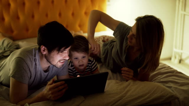 happy family with little son lying in bed at home and surfing social media on tablet computer before sleeping - family home video stock e b–roll