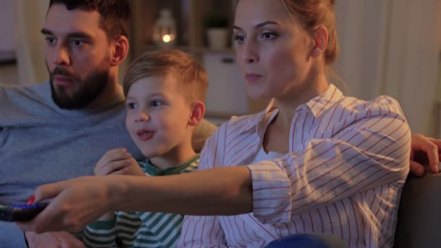 happy family with popcorn watching tv at home family, leisure and people concept - happy smiling father, mother and little son eating popcorn and watching tv at home in evening changing channels stock videos & royalty-free footage