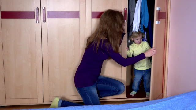 Happy family woman find her toddler child daughter in wardrobe closet video