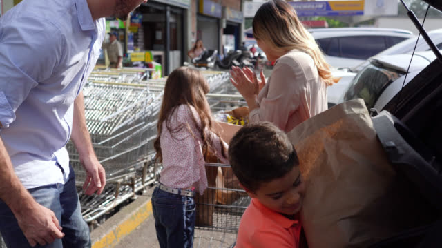 Happy family working together placing shopping bags from cart to trunk outside the supermarket Happy family working together placing shopping bags from cart to trunk outside the supermarket all smiling car shopping stock videos & royalty-free footage