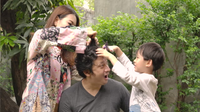 vídeos de stock e filmes b-roll de happy family young asian woman and her son trying to does haircuts to her husband with scissors at home because of lockdown. stay at home quarantine coronavirus pandemic prevention, social isolation concept. - covid hair