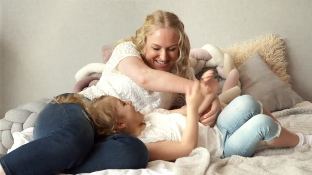 happy family, young attractive blonde mother with little 5 year old daughter lie on bed at home play, fool and laugh, mother tickles child girl. - fare il solletico video stock e b–roll