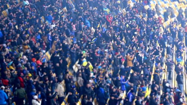 幸せなファンがフィールドでサッカー選手を拍手とスタジアム、ゲーム オーバーを残して - 観客点の映像素材/bロール